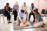First Aid Instructor Showing CPR Training On Dummy