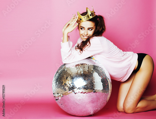 Naklejka young cute disco girl on pink background with disco ball and cro