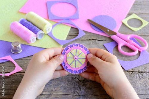 Small child made a simple and colorful flower from felt circles and beads. Child holds a bright felt flower in hands. Craft supplies on wooden table. Easy and fun teaching small kids to sew by hand