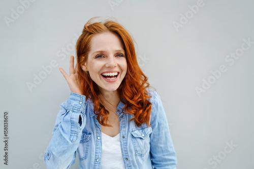 Leinwandbild Motiv lachende frau hält eine hand hinter ihr ohr