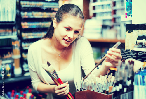 Positive woman shopping various paintbrushes Poster