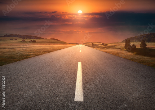 Poster Empty road through mountain scenery at idyllic sunset