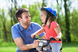 Girl learning to ride a bicycle with father  - 158121011