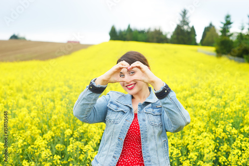 A young woman in rapeseed field.