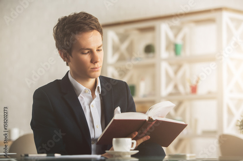Attractive guy drinking coffee and reading book