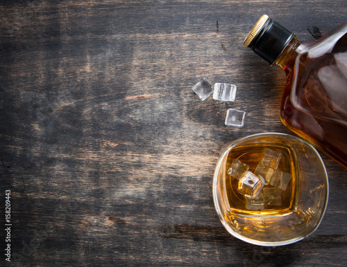 Glass with ice cubes and whiskey bottle on wooden table,top view