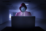 Hacker with mask in front of a laptop - 158215697