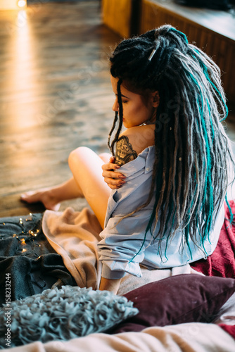 Beautiful woman with dreadlocks and tattoos. Boho style. The view from the back - 158233244