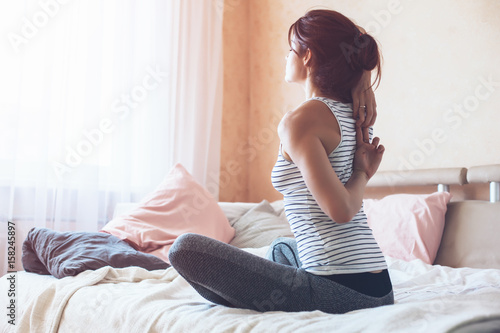 Fototapeta Woman doing yoga in the bed