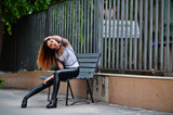 Fashionable woman look at white shirt, black transparent clothes, leather pants, posing at street sitting on bench against iron fence. Concept of fashion girl.