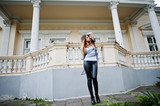 Fashionable woman look at white shirt, black transparent clothes, leather pants, posing at street against old house with windows and columns. Concept of fashion girl.