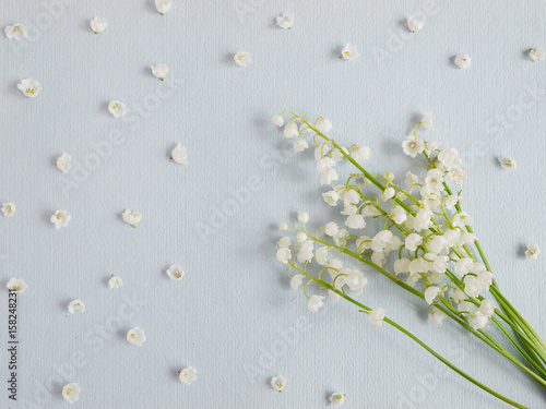 Fotobehang Lelietjes van dalen Lily of the valley on a blue paper textured background. Pattern of small flowers of the may-lily. Abstract floral background.