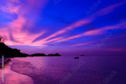 Fotobehang Violet Landscape view of sunset at the beach with dramatic sky and sun light ray.