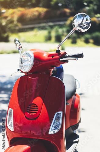 Foto op Canvas Scooter Close up red color vintage scooter in city summer street, hipster motorcycle on urban background, transport bike for tourism and travel adventure, holiday concept