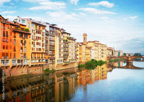 Poster old town houses reflecting in river Arno waters at summer day, Florence, Italy,