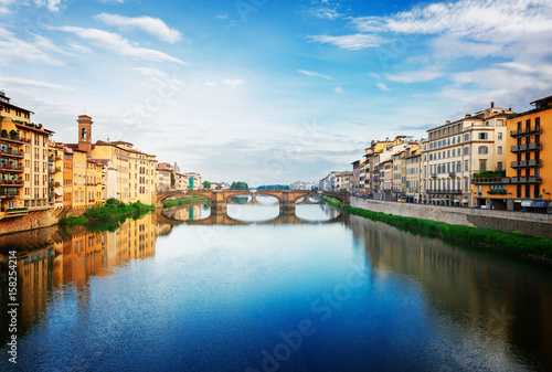 Poster old town with bridge Santa trinita reflecting in water of river Arno, Florence,