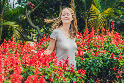 Foto op Canvas Azalea Young woman on the background of red salvia splendens flowers blooming in the garden