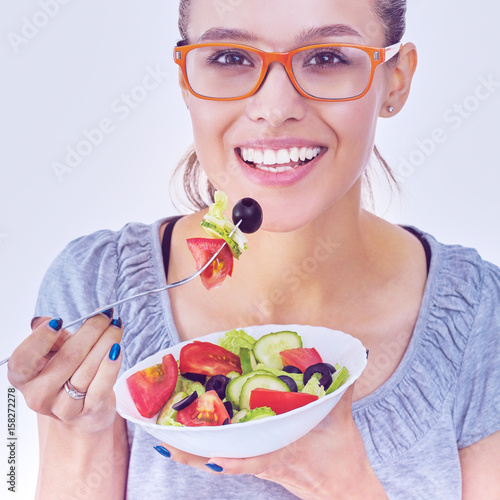 A beautiful girl eating healthy food , holding a plate