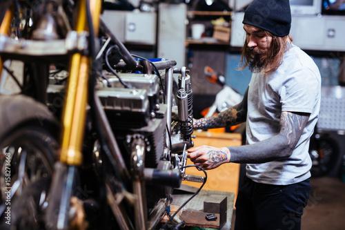 Deurstickers Fietsen Side view portrait of bearded tattooed mechanic working in garage customizing motorcycle and repairing broken parts