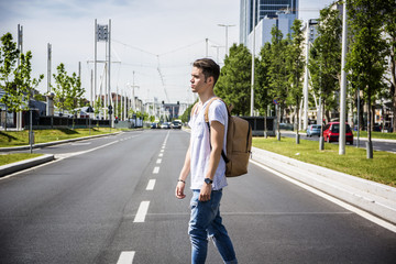 Attractive smiling man standing in the middle of city street looking straight ahead, with backpack