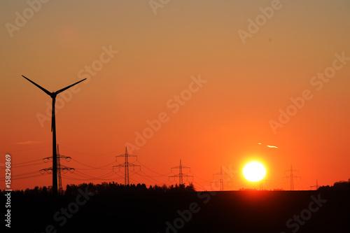 Papiers peints Orange eclat Windrad mit Strommast und Hochspannungsleitungen im Abendrot, Sonnenuntergang