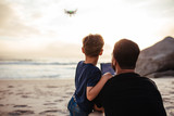 Fototapeta Father and son flying drone at the beach