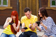 Group of three friends play mobile video game outdoors, girl and guy loose,dark haired girl wins