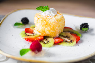 Close-up of a trendy dessert, fried ice cream with kiwi and strawberries, raspberries and blackberries, decorated with mint, sweet delicious, beautiful serve, restaurant