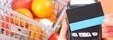 Payment terminal with contactless credit card and fruits and vegetables, concept of cashless paying for shopping