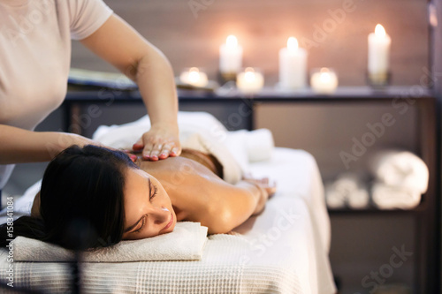 Fototapeta Body massage and spa treatment in modern salon with candles