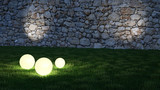 Glowing spheres in garden with wall in background - 158344252