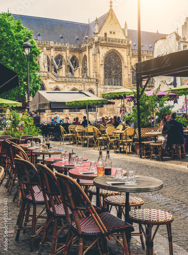 Fototapeta Cozy street with tables of cafe in Paris, France