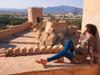 Quadro Girl sitting on stones on background of a beautiful old fortress in Oman.
