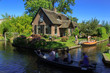 Giethoorn, The Netherlands, August 2016 Touristic boats in Giethoorn canal and beautiful cottages on shore. Giethoorn, known as the Venice of Holland is a beautiful village in the Netherlands.