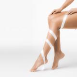 Fototapeta Women's legs with white ribbon