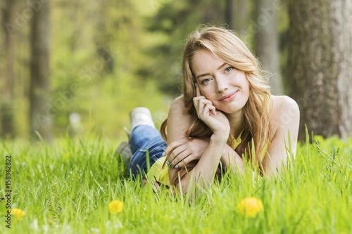 Woman lying on dandelions field
