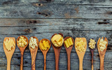 Italian foods concept and menu design. Various kind of Pasta Farfalle, Pasta A Riso, Orecchiette Pugliesi, Gnocco Sardo and Farfalle in wooden spoons setup on shabby wooden background with flat lay. - 158365607