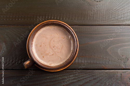 Papiers peints Chocolat Hot chocolate or cocoa drink in clay cup, on dark brown wooden table, top view