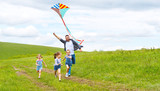 happy family father and children run with kite on meadow