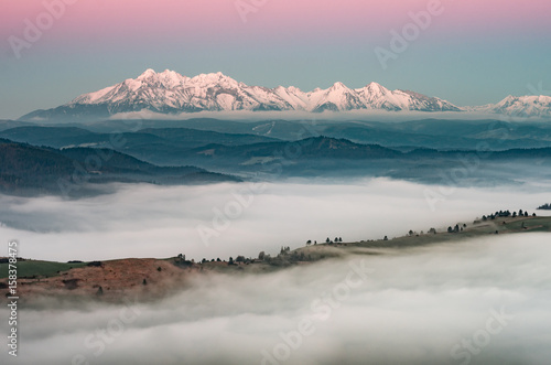 Foto op Canvas Lichtroze Beautiful spring panorama over misty Spisz highland to snowy Tatra mountains in the morning, Poland