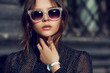 Outdoor close up portrait of young beautiful fashionable girl posing in street. Model wearing stylish sunglasses, white wrist watch, black polka dot blouse. City lifestyle. Female fashion concept