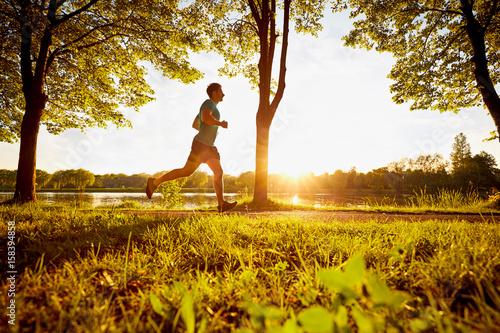 Fototapeta Young man running in park during sunset