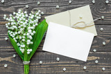 blank white greeting card and envelope with white lily of the valley flowers