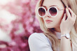 Outdoor close up portrait of young beautiful fashionable girl posing in street. Model wearing stylish white round sunglasses, wrist watch. Female fashion concept. Copy, empty space for text. Toned