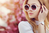 Outdoor close up portrait of young beautiful fashionable girl posing in street. Model wearing stylish white round sunglasses, wrist, hand watch. Female fashion concept. Copy, empty space for text - 158415452