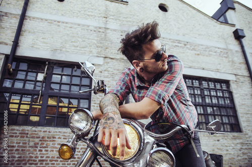 Portrait of handsome tattooed man with sunglasses on motorcycle, closeup