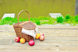Picnic on the nature in the forest near the river. Wooden table and fruit basket