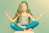 Girl with long hair and in jeans meditating in a lotus pose. Toned