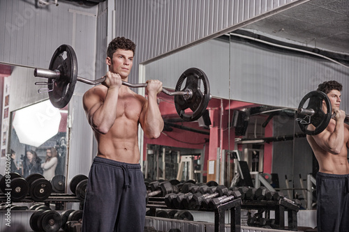 Exercising in the gym with heavy weights. Lifting heavy weights. Bodybuilder workout