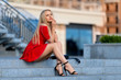 Woman in red dress sitting on the stairs